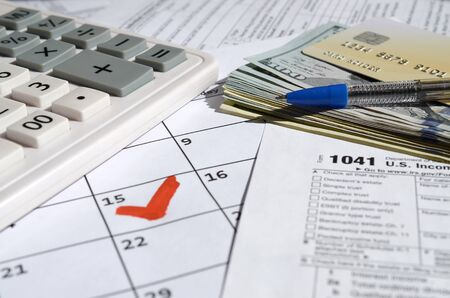1041 Income Tax Return for Estates and Trusts blank with dollar bills, calculator and pen on calendar page with marked 15th April. Tax period concept. IRS Internal Revenue Service 写真素材 - 132116841