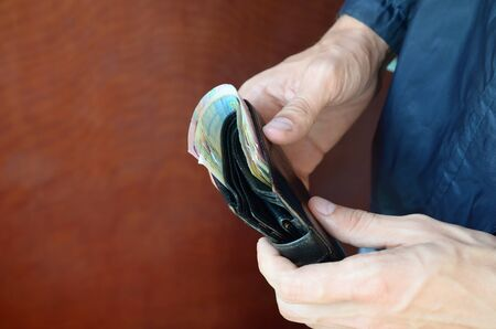 Man holds in hands black leather wallet with ukrainian money or thief who stole wallet full of money. Ukrainian economic crisis and crime concept