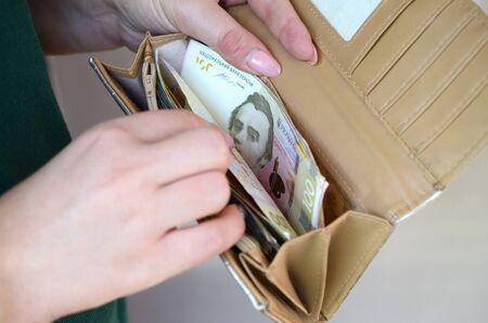 Female hands holding ukrainian hryvnia bills in small money pouch or wallet. Small salary in ukrainian economics concept. Poor life in ukraine 写真素材 - 132116845