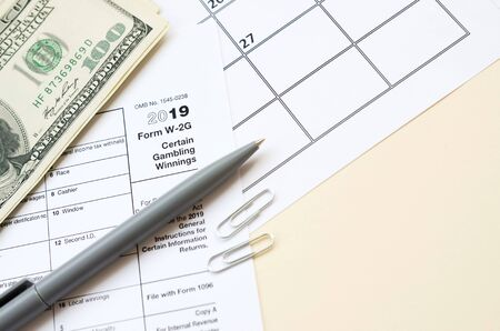 IRS Form W-2G Certain Gambling Winning blank lies with pen and many hundred dollar bills on calendar page. Tax period concept. Copy space for text 写真素材 - 132116906