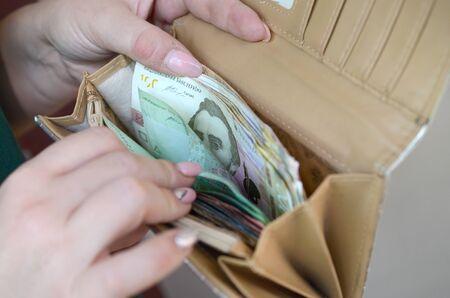 Female hands holding ukrainian hryvnia bills in small money pouch or wallet. Small salary in ukrainian economics concept. Poor life in ukraine 写真素材