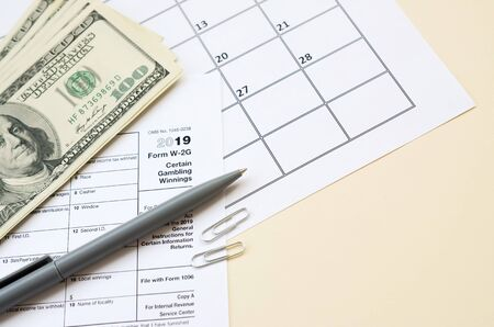IRS Form W-2G Certain Gambling Winning blank lies with pen and many hundred dollar bills on calendar page. Tax period concept. Copy space for text