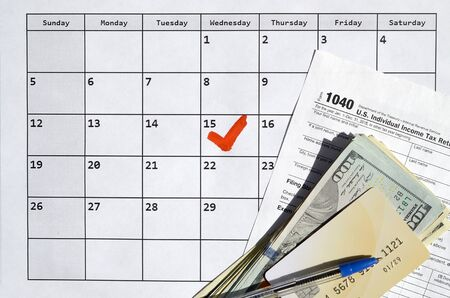 1040 Individual Income Tax Return blank with credit card on dollar bills and pen on calendar page with marked 15th April. Tax period concept. IRS Internal Revenue Service 写真素材 - 132117010