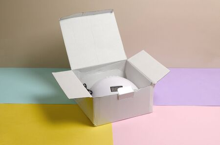 Unboxing of new UV LED nail lamp for curing process by gel method. Cardboard box on pastel multi colored table.