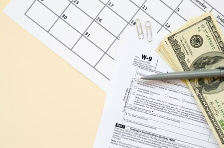 IRS Form W-9 Request for taxpayer identification number and certification blank lies with pen and many hundred dollar bills on calendar page. Tax period concept. Copy space for text