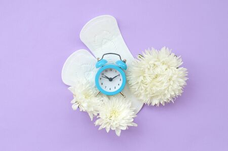 Blue alarm clock and white flowers lies on menstrual pads on pastel lilac background. Aspects of women wellness in monthlies period. Woman critical days gynecological menstruation cycle. Flat lay