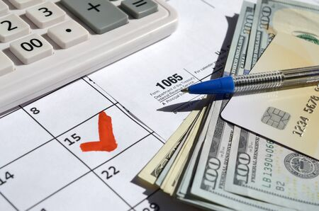 1065 Return of partnership income blank with dollar bills, calculator and pen on calendar page with marked 15th April. Tax period concept. IRS Internal Revenue Service 写真素材 - 132117042