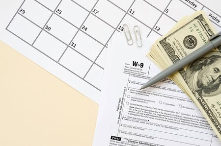 IRS Form W-9 Request for taxpayer identification number and certification blank lies with pen and many hundred dollar bills on calendar page. Tax period concept. Copy space for text Фото со стока - 132117069
