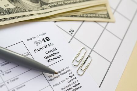 IRS Form W-2G Certain Gambling Winning blank lies with pen and many hundred dollar bills on calendar page. Tax period concept. Copy space for text 写真素材 - 132117066