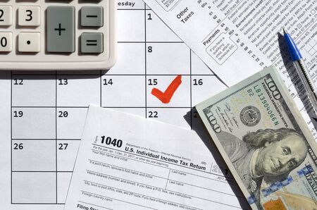 1040 Individual Income Tax Return blank with dollar bills, calculator and pen on calendar page with marked 15th April. Tax period concept. IRS Internal Revenue Service 写真素材