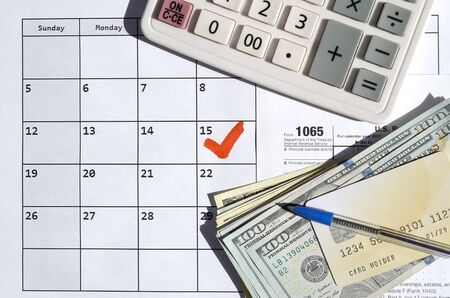 1065 Return of partnership income blank with dollar bills, calculator and pen on calendar page with marked 15th April. Tax period concept. IRS Internal Revenue Service 写真素材 - 132117072