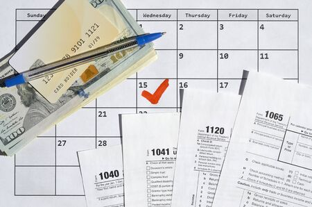 Many most important tax form blanks with credit card on dollar bills and pen on calendar page with marked 15th April. Tax period concept. IRS Internal Revenue Service