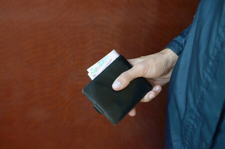 Man holds in hands black leather wallet with ukrainian money or thief who stole wallet full of money. Ukrainian economic crisis and crime concept Фото со стока - 132117076