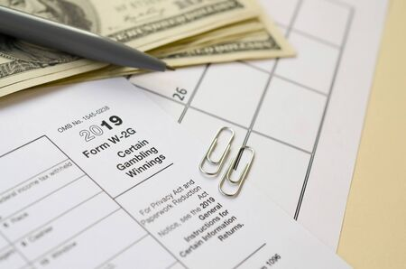 IRS Form W-2G Certain Gambling Winning blank lies with pen and many hundred dollar bills on calendar page. Tax period concept. Copy space for text Фото со стока - 132117086