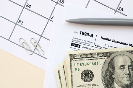 IRS Form 1095-A Health Insurance Marketplace Statement tax blank lies with pen and many hundred dollar bills on calendar page. Tax period concept. Copy space for text