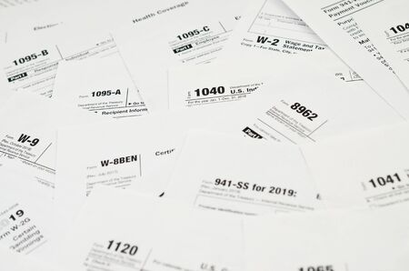 Many tax form blanks lies on table close up. Tax payers paperwork routine and bureaucracy concept. Need help with tax problems 写真素材 - 132117291
