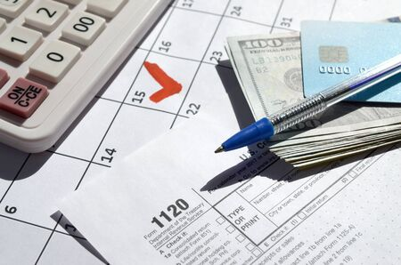 1120 Corporation Income Tax Return blank with credit card on dollar bills, calculator and pen on calendar page with marked 15th April. Tax period concept. IRS Internal Revenue Service