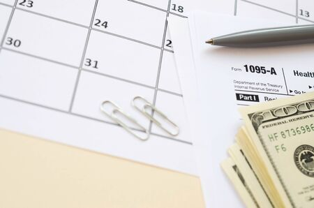 IRS Form 1095-A Health Insurance Marketplace Statement tax blank lies with pen and many hundred dollar bills on calendar page. Tax period concept. Copy space for text Фото со стока - 132117433