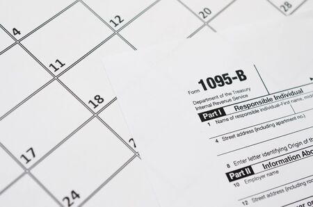 IRS Form 1095-B Health Coverage tax blank lies on empty calendar page. Tax period concept. Copy space for text Фото со стока - 132117435