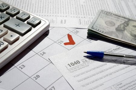 1040 Individual Income Tax Return blank with dollar bills, calculator and pen on calendar page with marked 15th April. Tax period concept. IRS Internal Revenue Service Stockfoto