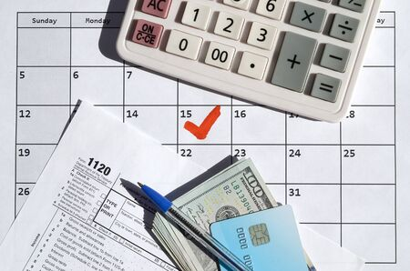 1120 Corporation Income Tax Return blank with credit card on dollar bills, calculator and pen on calendar page with marked 15th April. Tax period concept. IRS Internal Revenue Service Фото со стока - 132117439