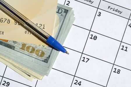 Pen and credit card on many hundred US dollar bills on calendar page close up. Business and financial planning concept. Accountant work Фото со стока - 132117441