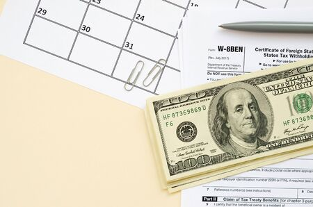 IRS Form W-8BEN Certificate of foreign status of beneficial owner for United States tax withholding and reporting for individuals blank lies with pen and many hundred dollar bills on calendar page