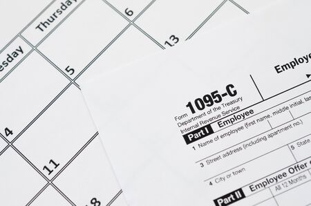 IRS Form 1095-C Employer-Provided Health Insurance Offer and Coverage tax blank lies on empty calendar page. Tax period concept. Copy space for text
