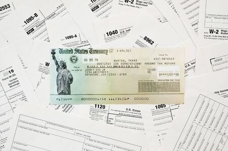 Refund check on many tax form blanks lies on table close up. Tax payers paperwork routine and bureaucracy concept. Need help with tax problems Фото со стока - 132117547
