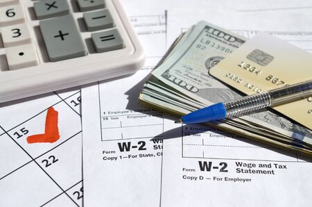 W-2 Wage and Tax statement blank with credit card on dollar bills, calculator and pen on calendar page with marked 15th April. Tax period concept. IRS Internal Revenue Service 写真素材