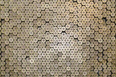 Pattern of 12 gauge cartridges for shotgun bullets. Shells for hunting rifle close up. Backdrop for shooting range or ammunition trade concepts. Used 12 caliber cylinder cooper caps in stack Фото со стока - 132117625