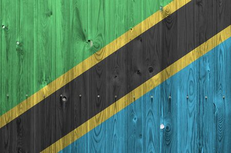 Tanzania flag depicted in bright paint colors on old wooden wall close up. Textured banner on rough background