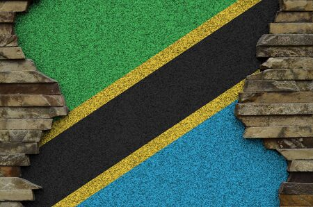 Tanzania flag depicted in paint colors on old stone wall close up. Textured banner on rock wall background Stock fotó