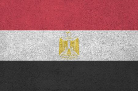 Egypt flag depicted in bright paint colors on old relief plastering wall close up. Textured banner on rough background