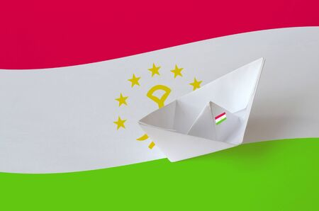 Tajikistan flag depicted on paper origami ship closeup. Oriental handmade arts concept