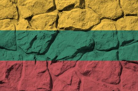 Lithuania flag depicted in paint colors on old stone wall close up. Textured banner on rock wall background Stock fotó