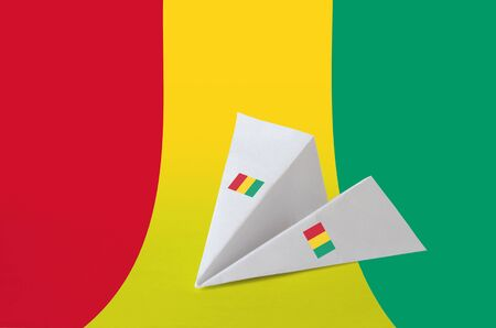 Guinea flag depicted on paper origami airplane. Oriental handmade arts concept