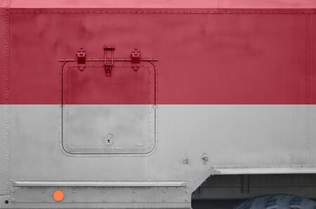 Indonesia flag depicted on side part of military armored truck close up. Army forces vehicle conceptual background
