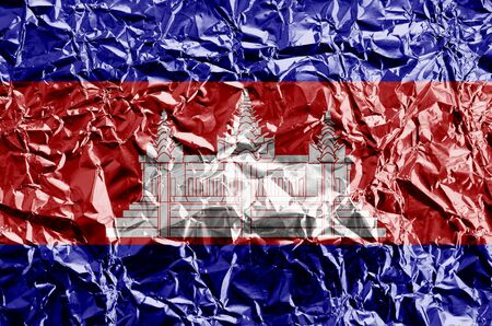 Cambodia flag depicted in paint colors on shiny crumpled aluminium foil close up. Textured banner on rough background Reklamní fotografie