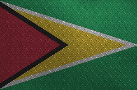 Guyana flag depicted in paint colors on old brushed metal plate or wall close up. Textured banner on rough background