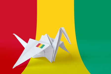 Guinea flag depicted on paper origami crane wing. Oriental handmade arts concept