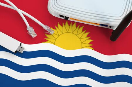 Kiribati flag depicted on table with internet rj45 cable, wireless usb wi-fi adapter and router. Internet connection concept