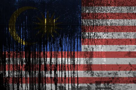 Malaysia flag depicted in paint colors on old and dirty oil barrel wall close up. Textured banner on rough background
