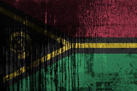 Vanuatu flag depicted in paint colors on old and dirty oil barrel wall close up. Textured banner on rough background Banco de Imagens