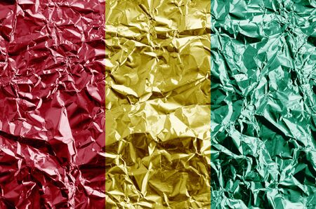 Guinea flag depicted in paint colors on shiny crumpled aluminium foil close up. Textured banner on rough background