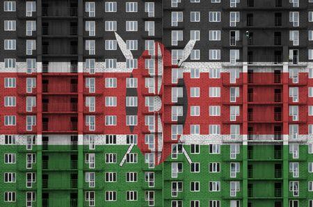 Kenya flag depicted in paint colors on multi-storey residental building under construction. Textured banner on big brick wall background Standard-Bild