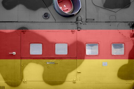 Germany flag depicted on side part of military armored helicopter close up. Army forces aircraft conceptual background 스톡 콘텐츠