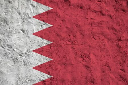 Bahrain flag depicted in bright paint colors on old relief plastering wall close up. Textured banner on rough background