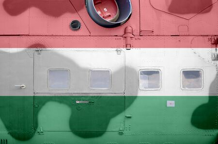 Hungary flag depicted on side part of military armored helicopter close up. Army forces aircraft conceptual background 스톡 콘텐츠