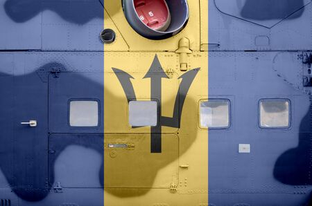 Barbados flag depicted on side part of military armored helicopter close up. Army forces aircraft conceptual background